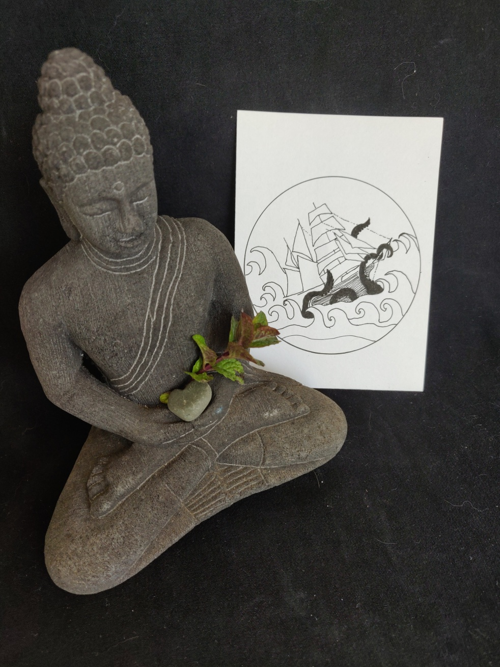 meditating statue with sprig of mint and drawing of a ship in rough waves and kraken tentacles grabbing the ship